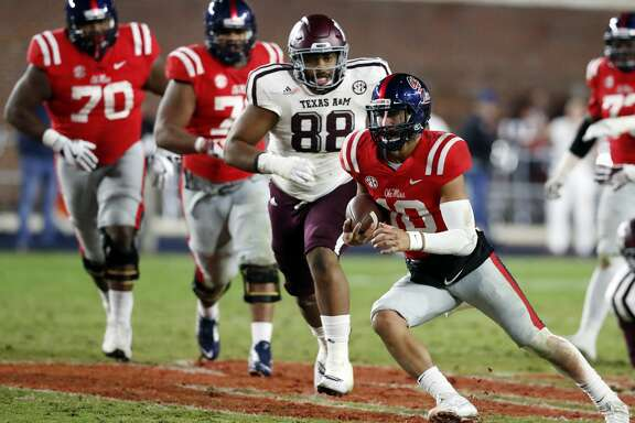 Mississippi quarterback Jordan Ta'amu (10) is pursued by Texas A&M defensive lineman Kingsley Keke (88) after outrunning his offensive line during the second half of an NCAA college football game against Texas A&M in Oxford, Miss., Saturday, Nov. 18, 2017. Texas A&M won 31-24. (AP Photo/Rogelio V. Solis)