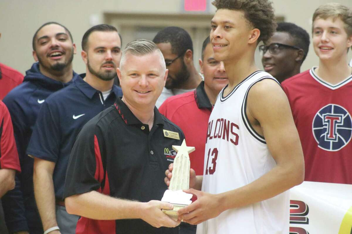 Steering committee member Chris Bezdek presents the MVP trophy to Katy Tompkins' C.J. Washington, following the team's 59-54 championship-game win over Duncanville Saturday night.