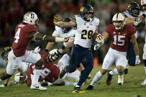 California�s Patrick Laird (28) runs between Stanford�s Alameen Murphy (4) and Jordan Perez (15) during the second quarter the 120th Big Game,  Saturday, Nov. 18, 2017 in Stanford, Calif.