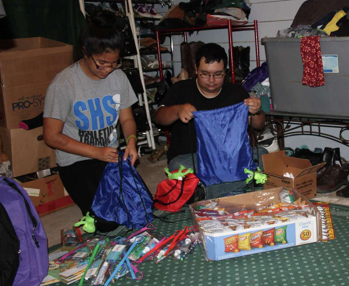 Dyanne Vasquez (left) and Teddy Elliot (right) of the Impact Center put together supplies to be given out to the homeless for Christmas.
