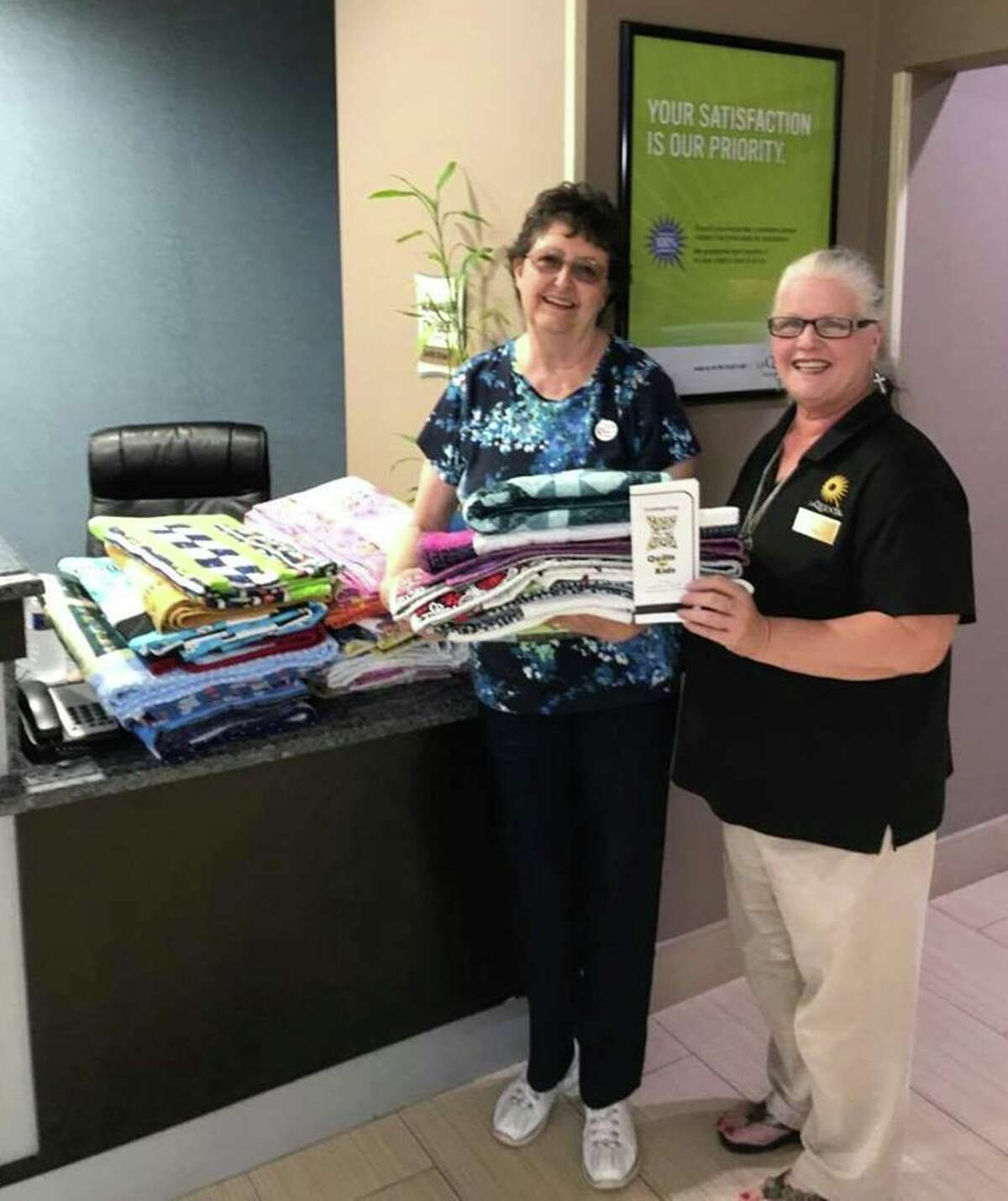 Linda Deeter (left) of the Coldspring chapter of Quilts for Kids bringsa stack of quilts to the LaQuinta Inn located in Cleveland to be given to children displaced from their homes after the floods of Hurricane Harvey.
