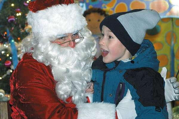 Rinat Reed of Middletown recounts his wish list to Santa (Al Santostefano) during Holiday on Main Street in this archive shot.