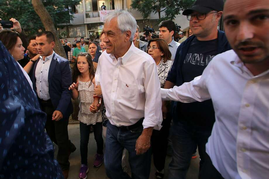Candidate Sebastián Piñera (center) arrives at a polling station in Santiago, Chile. Piñera, a Harvard-educated entrepreneur, previously served as president from 2010 to 2014. Photo: CLAUDIO REYES, AFP/Getty Images