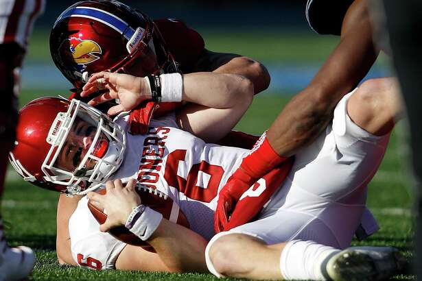 LAWRENCE, KS - NOVEMBER 18:  Quarterback Baker Mayfield #6 of the Oklahoma Sooners is sacke during the game against the Kansas Jayhawks at Memorial Stadium on November 18, 2017 in Lawrence, Kansas.