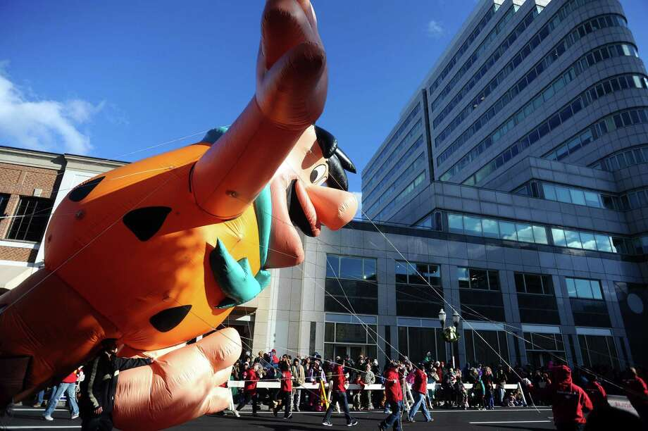 Fred Flintstone glides down Atlantic Street during the 24th annual Stamford Downtown Parade Spectacular in downtown Stamford, Conn. on Sunday, Nov. 19, 2017. Photo: Michael Cummo / Hearst Connecticut Media / Stamford Advocate