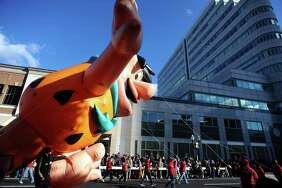 Fred Flintstone glides down Atlantic Street during the 24th annual Stamford Downtown Parade Spectacular in downtown Stamford, Conn. on Sunday, Nov. 19, 2017.