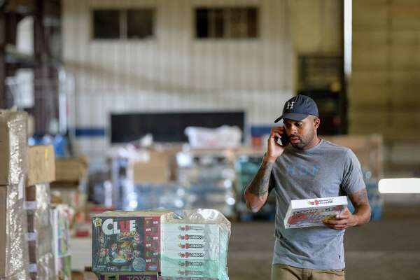 """Justin Rogers, who goes by his performer name, """"DJ Mr. Rogers,"""" looks through donated items in a warehouse he and a friend, Frazier Thompson, III, use for their charity operations, Monday, Nov. 6, 2017, in Houston."""