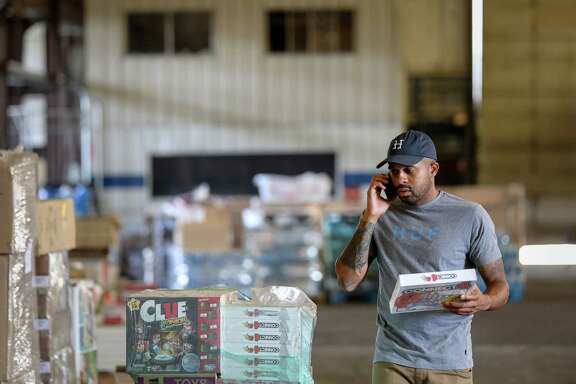 "Justin Rogers, who goes by his performer name, ""DJ Mr. Rogers,"" looks through donated items in a warehouse he and a friend, Frazier Thompson, III, use for their charity operations, Monday, Nov. 6, 2017, in Houston."