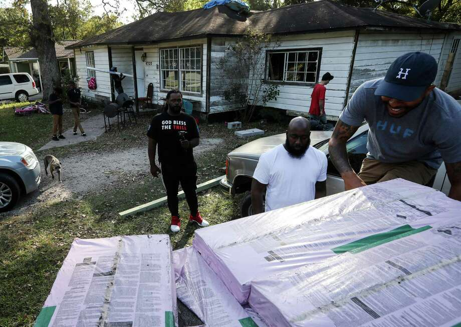 "Justin Rogers, from right, who goes by his performer name, ""DJ Mr. Rogers,"" Frazier Thompson, III, who goes by his stage name, ""Trae the Truth, and T.J. Smith, unload building supplies at a home in the Acres Homes area that was damaged by Hurricane Harvey, Monday, Nov. 6, 2017, in Houston. Rogers and Thompson use their non-profit organization to distribute supplies to victims of Hurricane Harvey. Photo: Jon Shapley, Houston Chronicle / © 2017 Houston Chronicle"