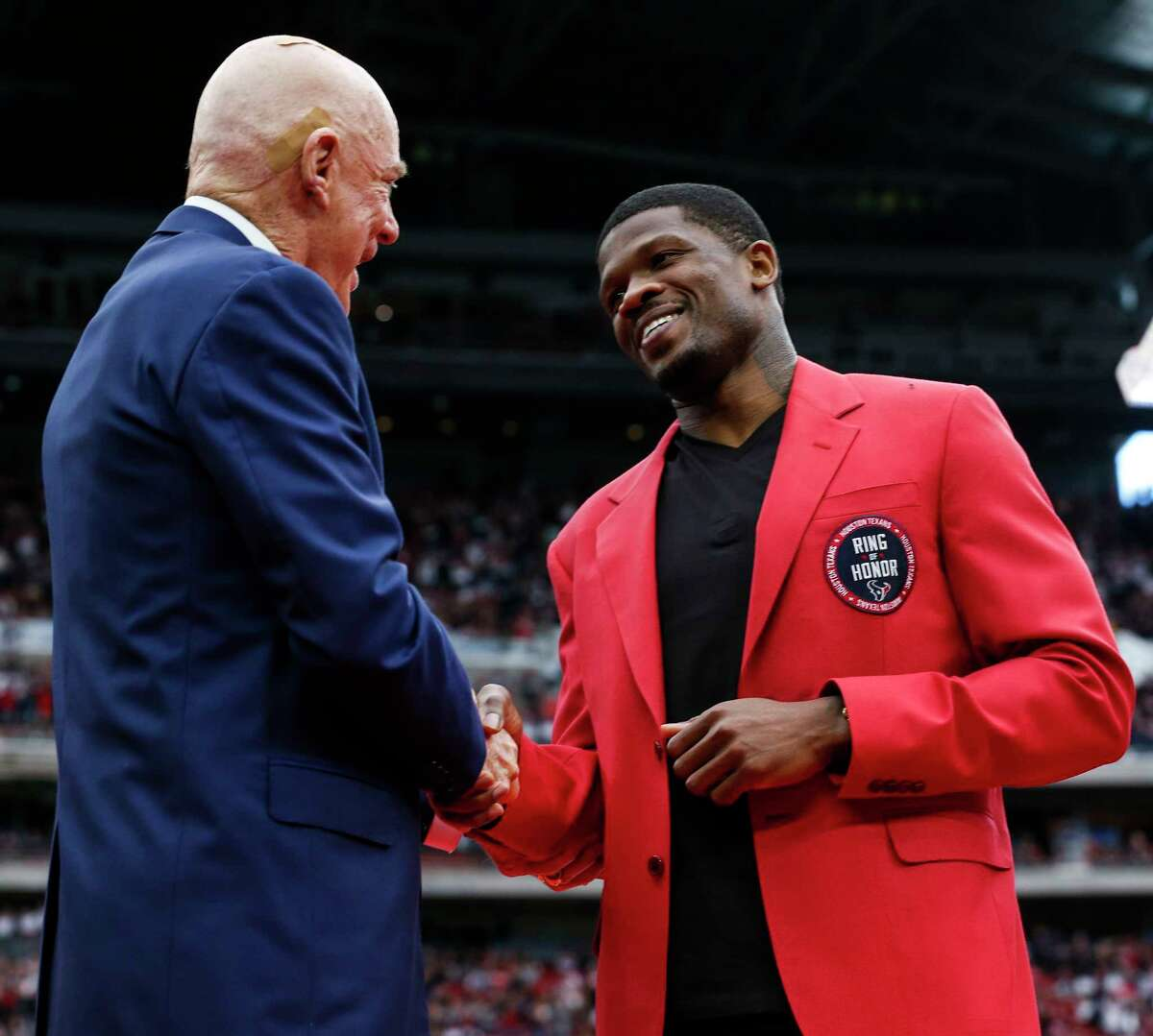 Houston Texans owner Bob McNair shankes hands with former Texans wide receiver Andre Johnson waves to the fans as he is honored as the first Texans player in the Ring of Honor during the halftime celebration at NRG Stadium on Sunday, Nov. 19, 2017, in Houston.