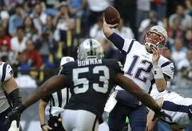 New England Patriots quarterback Tom Brady (12) passes under pressure from Oakland Raiders middle linebacker NaVorro Bowman (53) during the first half of an NFL football game Sunday, Nov. 19, 2017, in Mexico City. (AP Photo/Rebecca Blackwell)