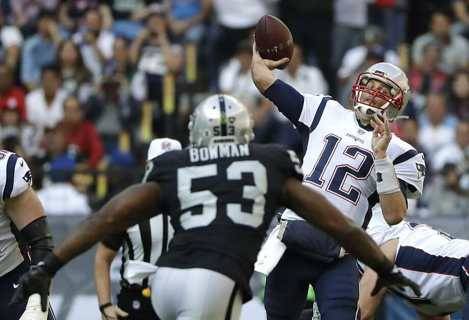 New England Patriots quarterback Tom Brady (12) passes under pressure from Oakland Raiders middle linebacker NaVorro Bowman (53) during the first half of an NFL football game Sunday, Nov. 19, 2017, in Mexico City. (AP Photo/Rebecca Blackwell) Photo: Rebecca Blackwell, Associated Press