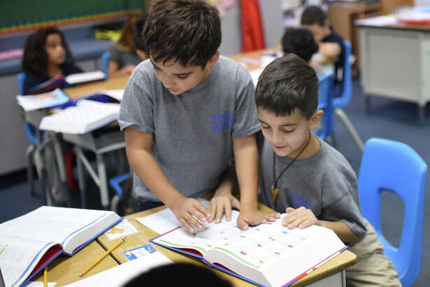 Washington STEM Academy third-graders Evan Galindo, left, and Lincoln Arterberry, check out the dictionaries they received on Friday.