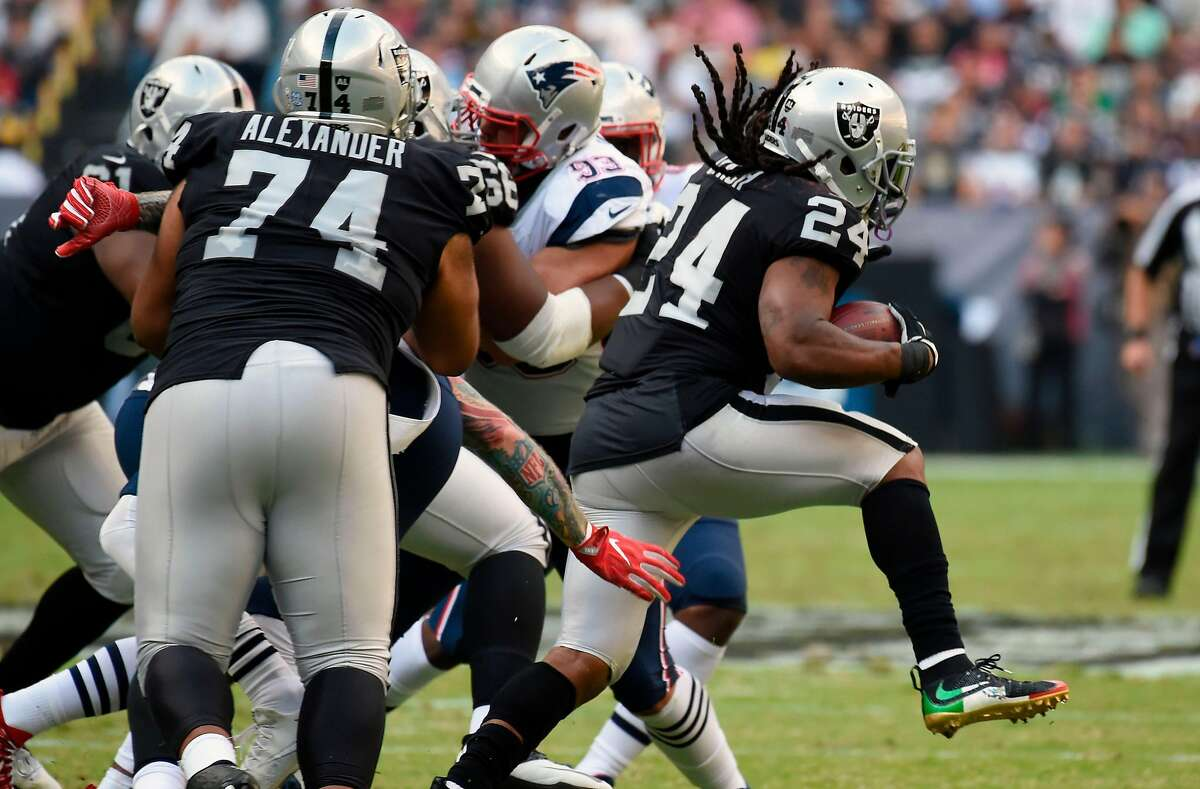 Oakland Raiders' Marshawn Lynch hands the ball off during the 2016 NFL week 11 regular season football game against New England Patriots on November 19, 2017 at the Azteca Stadium in Mexico City. / AFP PHOTO / ALFREDO ESTRELLAALFREDO ESTRELLA/AFP/Getty Images