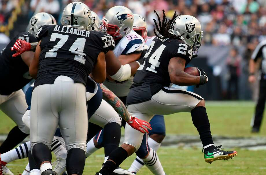 Oakland Raiders' Marshawn Lynch hands the ball off during the 2016 NFL week 11 regular season football game against New England Patriots on November 19, 2017 at the Azteca Stadium in Mexico City. / AFP PHOTO / ALFREDO ESTRELLAALFREDO ESTRELLA/AFP/Getty Images Photo: ALFREDO ESTRELLA, AFP/Getty Images