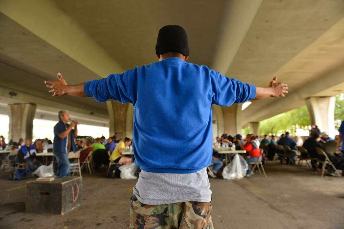 Frank Hernandez prays during the Church of Hope's twice-monthly lunch and ministering to the homeless underneath I35/I10.
