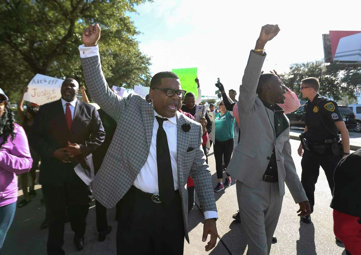 Protesters march down Kirby Drive to protest against Houston Texans owner Bob McNair's