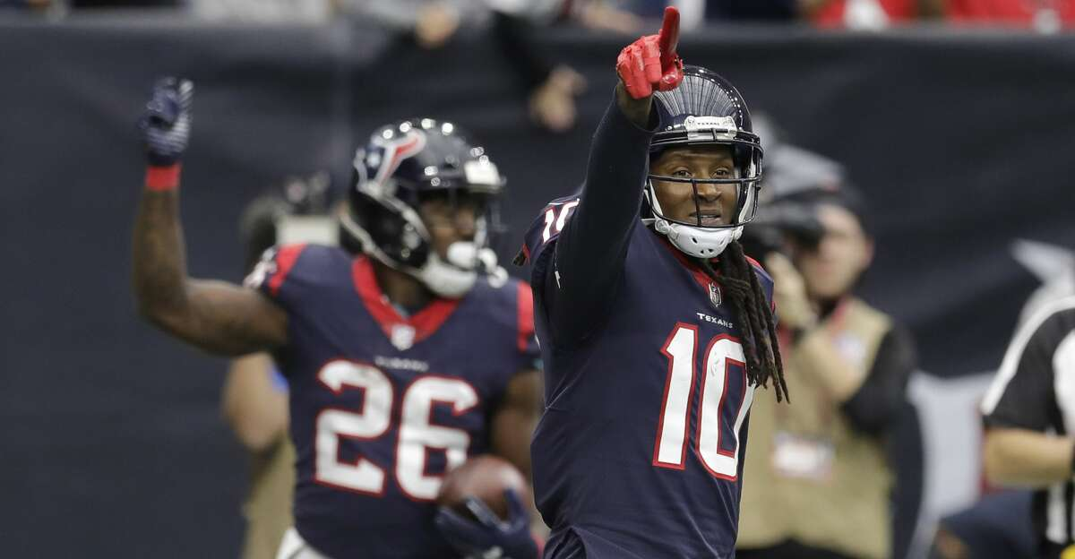 Houston Texans wide receiver DeAndre Hopkins (10) celebrates a touchdown catch by teammate Lamar Miller (26) during the first half of an NFL football game against the Arizona Cardinals, Sunday, Nov. 19, 2017, in Houston. (AP Photo/David J. Phillip)