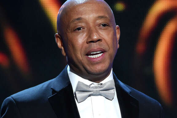 FILE - In this Feb. 6, 2015, file photo, hip-hop mogul Russell Simmons presents the Vanguard Award on stage at the 46th NAACP Image Awards in Pasadena, Calif. In a report published Sunday, Nov. 19, 2017, in the Los Angeles Times, Model Keri Claussen Khalighi accused Simmons of sexual misconduct in 1991 when she was 17-years-old. Simmons, denied the allegations in a statement. (Photo by Chris Pizzello/Invision/AP, File)