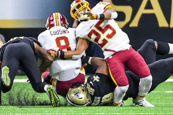 Redskins running back Chris Thompson (25) suffers a leg injury as Saints defensive tackle Sheldon Rankins (98) rolls up on it while tackling Kirk Cousins (8).