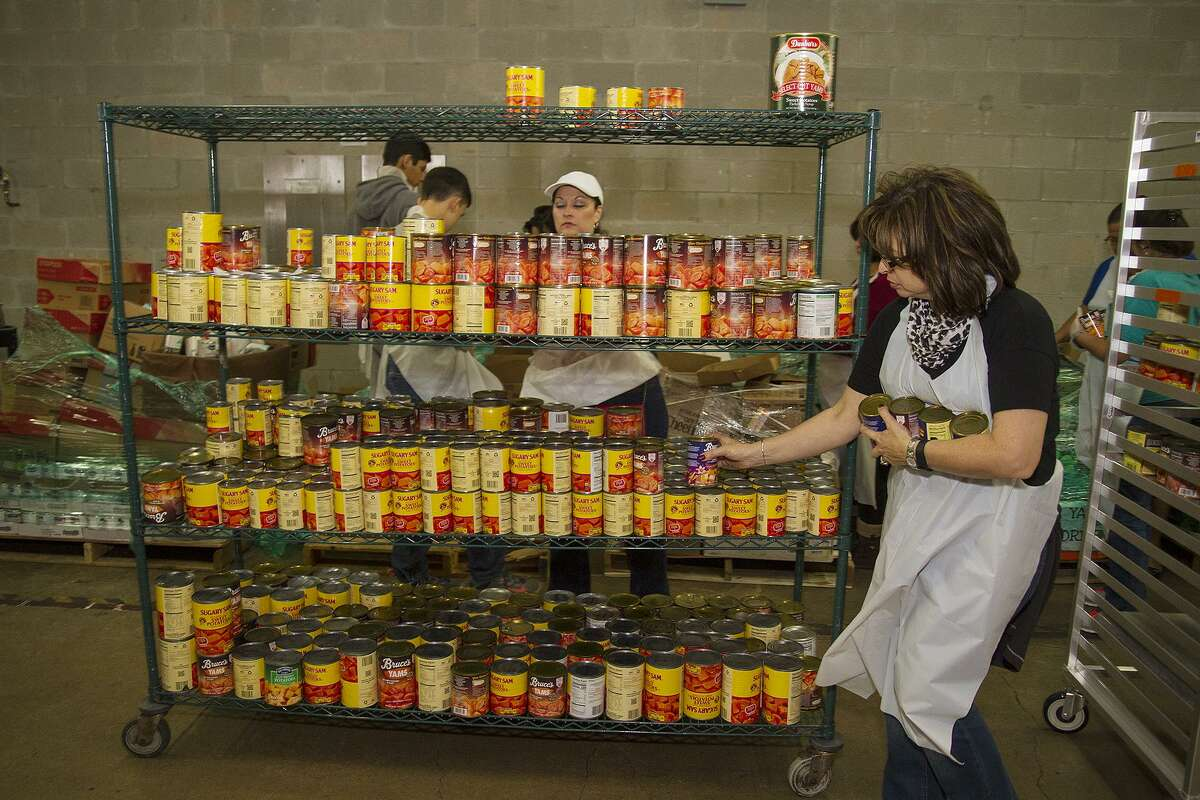 Volunteer Lisa Lozano with Antonian College Preparatory High School sorting canned goods at the convention center, Sunday, Nov. 19, 2017, in preparation for the Raul Jimenez Thanksgiving Dinner. Over 550 turkeys will be served at the annual event on Thursday.