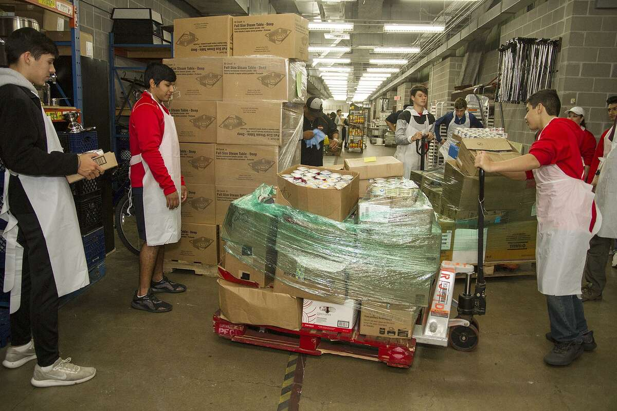 (Left to right) Volunteers James Merrit, 17, Ethan Holguin, 17, and Marcus Lozano, 14, football players at Antonian College Preparatory High School deliver pallets of cranberry at the convention center, Sunday, Nov. 19, 2017, in preparation for the Raul Jimenez Thanksgiving Dinner. Over 550 turkeys will be served at the annual event on Thursday.