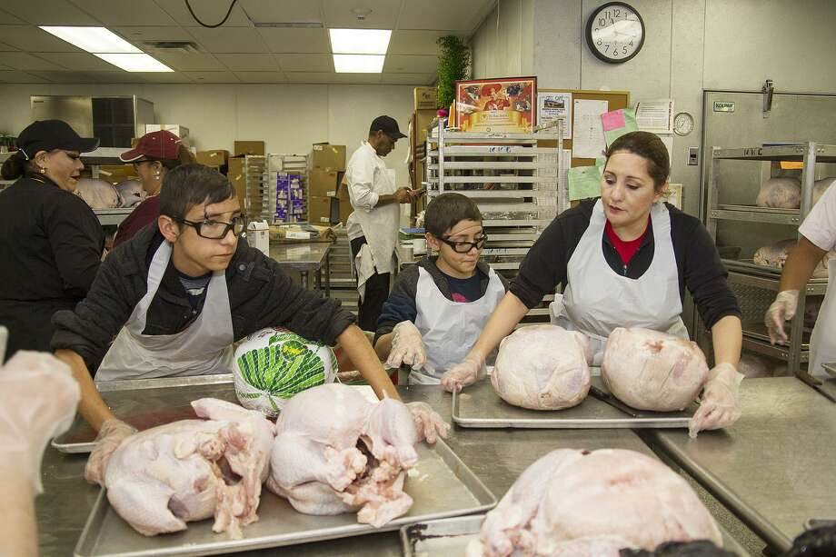 Volunteers Meloni Solis, right, with her sons, John Paul, 12, center, and Jesus, 14, prep turkeys for seasoning at the convention center, Sunday, Nov. 19, 2017 for the Raul Jimenez Thanksgiving Dinner. Over 550 turkeys will be served at the annual event on Thursday. Photo: Alma E. Hernandez, For The San Antonio Express News / Alma E. Hernandez / For The San Antonio Express News