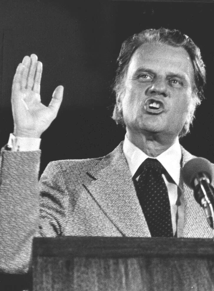 Billy Graham gestures during his May 14, 1976 crusade in the Seattle Kingdome before 74,000 people, which set an attendance record for the Kingdome.  (File Photo)