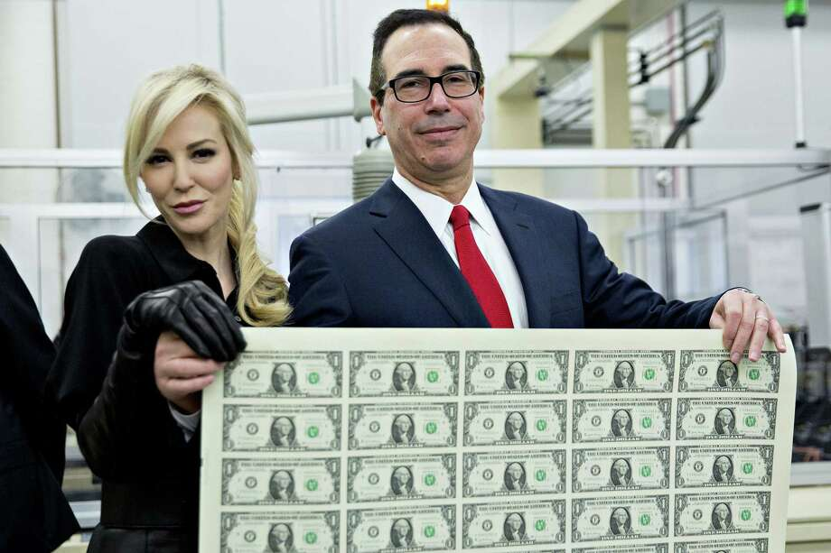 Treasury Secretary Steven Mnuchin, right, and wife, Louise Linton, hold an uncut sheet of $1 dollar notes. The new $1 bills, with Mnuchin and U.S. Treasurer Jovita Carranza's signatures, are expected to go into circulation in December. Photo: Andrew Harrer / Bloomberg