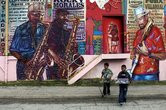 """D.J. Vela (left), 6, and Jeremiah Gonzalez, 9, collect donations for San Anto Cultural Arts during the community blessing for the mural """"La Musica de San Anto"""" in 2009."""
