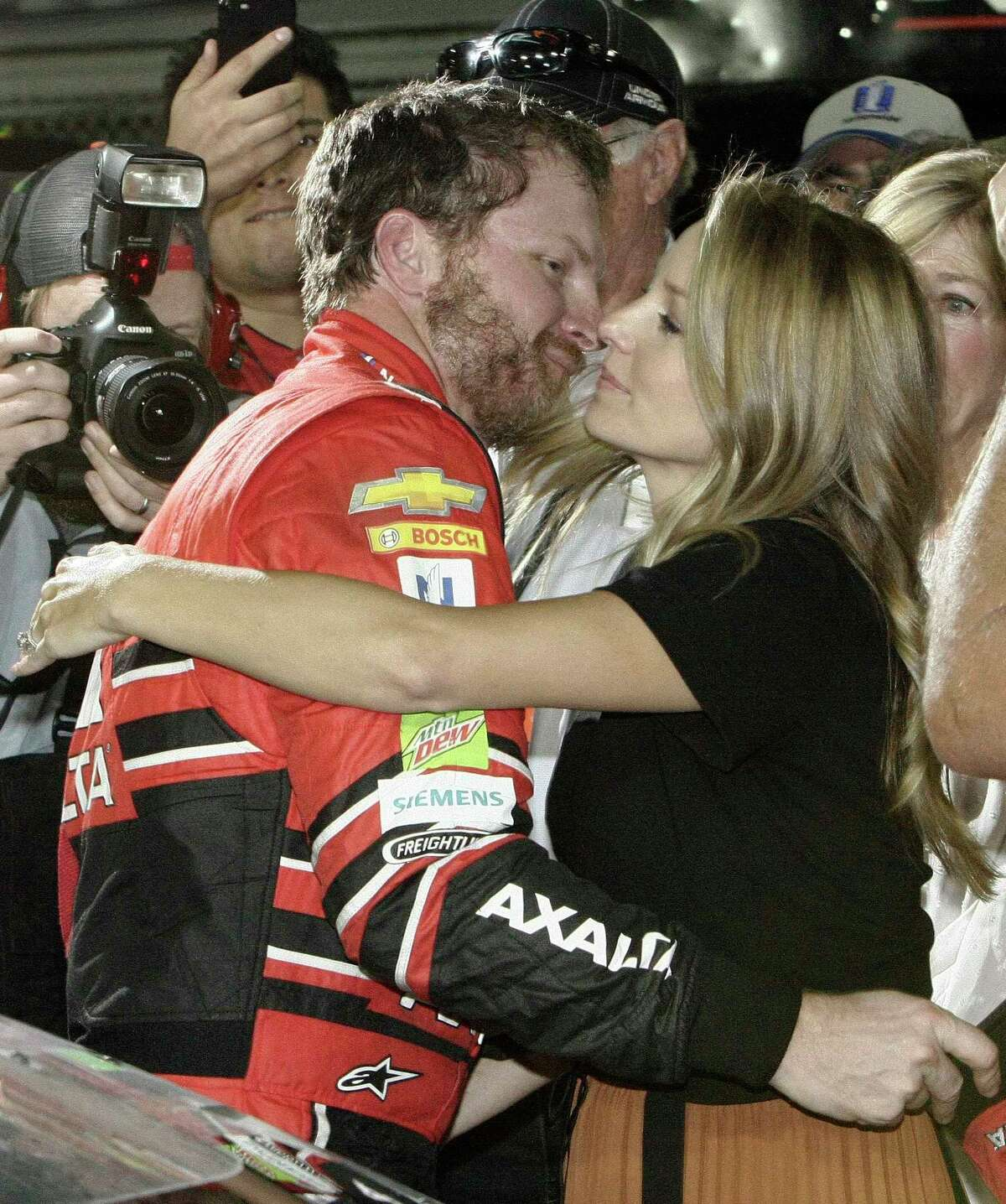 Dale Earnhardt Jr., left, hugs his wife Amy after getting out of his car at the end of a NASCAR Cup Series auto race at Homestead-Miami Speedway in Homestead, Fla., Sunday, Nov. 19, 2017. Earnhardt is retiring from full-time racing. (AP Photo/Terry Renna) ORG XMIT: FLTR110