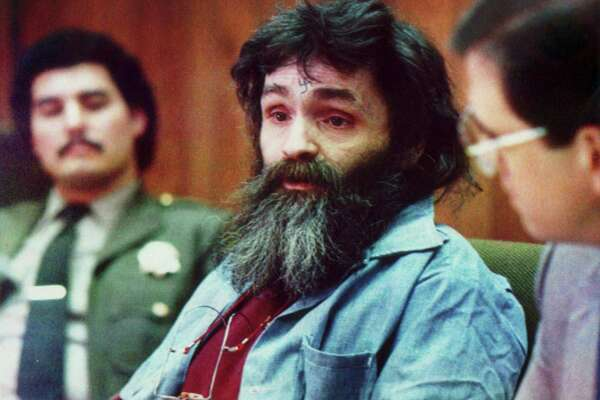 Charles Manson, wearing a swastika on his forehead, listens to the panel at his parole hearing in San Quentin prison in 1986.
