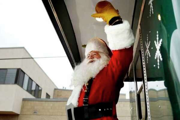 FILE -- Santa waives to the crowd during the annual Santa Parade.