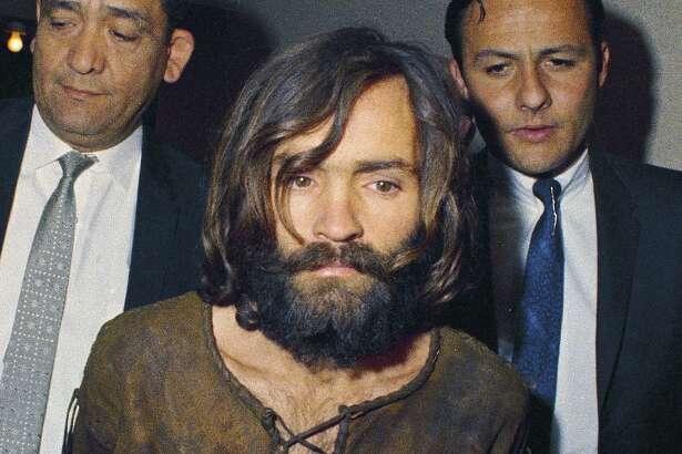 In this 1969 file photo, Charles Manson is escorted to his arraignment on conspiracy-murder charges in connection with the Sharon Tate murder case. He died Sunday at the age of 83.