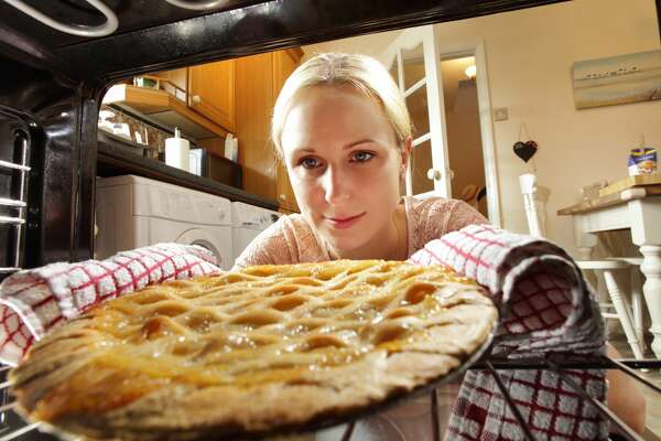 Woman taking apple pie out of oven