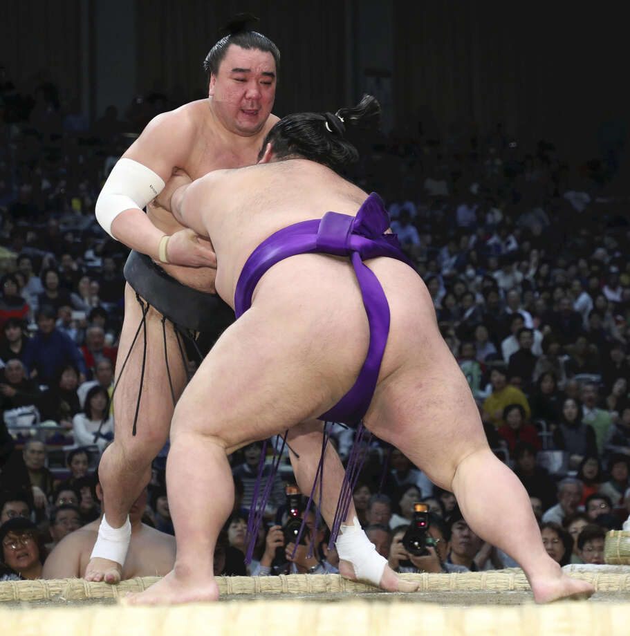 Sumo champion Harumafuji, left, shown in a recent match, is accused off  assaulting
