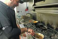 Chef Carl Carrion makes a braised short ribs appetizer in the Cask Republic's kitchen in Norwalk.