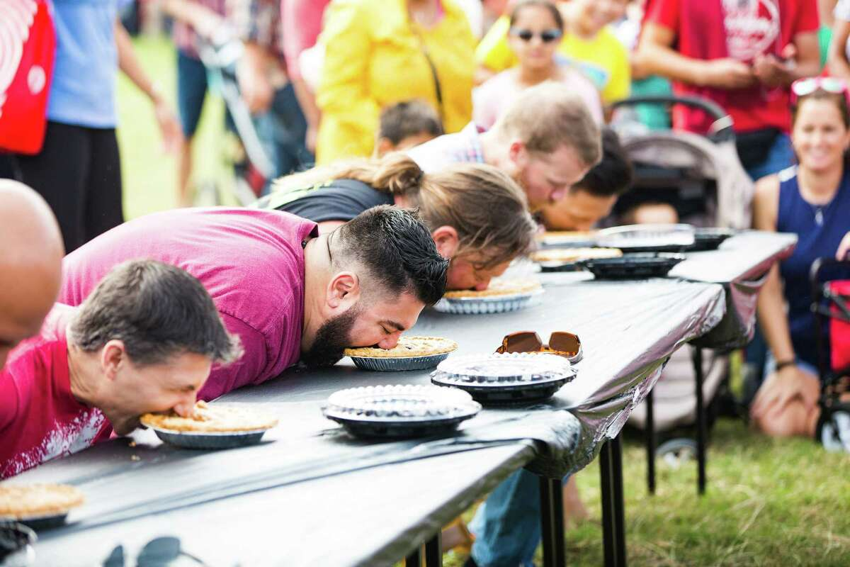 Competitors in the Harvest Fest pie-eating contest take their first bites to victory as crowds as well-wishers watch.