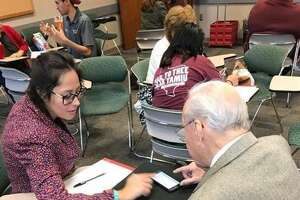 """A student volunteer assists one of the senior citizens enrolled in the technology course """"High Tech Seniors"""" offered at TAMIU."""