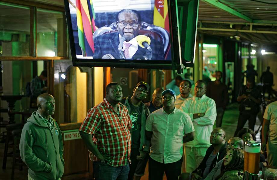 Zimbabweans watch a televised address to the nation by President Robert Mugabe at a bar in downtown Harare, Zimbabwe Sunday, Nov. 19, 2017. Zimbabwe's President Robert Mugabe has baffled the country by ending his address on national television without announcing his resignation. (AP Photo/Ben Curtis) Photo: Ben Curtis, Associated Press