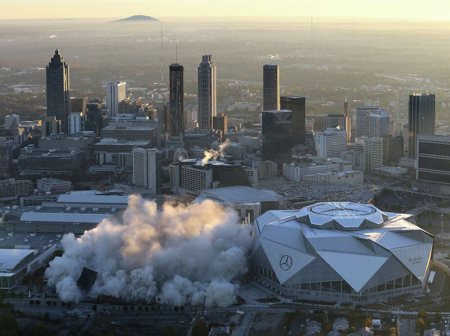 The Georgia Dome is destroyed in a scheduled implosion next to its replacement the Mercedes-Benz Stadium, right, Monday, Nov. 20, 2017, in Atlanta. The dome was not only the former home of the Atlanta Falcons but also the site of two Super Bowls, 1996 Olympics Games events and NCAA basketball tournaments among other major events. (Curtis Compton/Atlanta Journal-Constitution via AP) Photo: Curtis Compton, AP / Atlanta Journal-Constitution