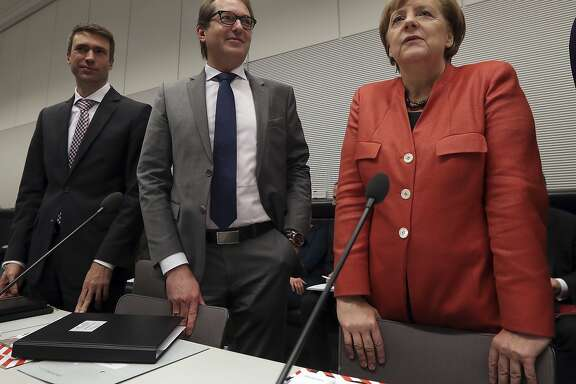 German Chancellor and Chairwomen of the German Christian Democratic Party (CDU), Angela Merkel, right, and the chairman of the German Christian Social Union state group, Alexander Dobrindt, center, arrive for a faction meeting at the German Federal Parliament, Bundestag, in the Reichstag building in Berlin, Germany, Monday, Nov. 20, 2017. (AP Photo/Michael Sohn)