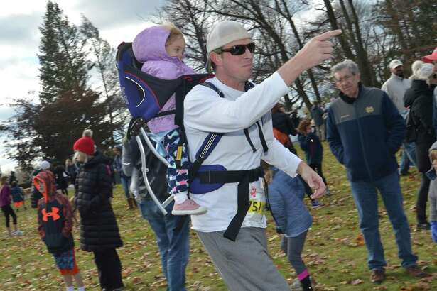 New Canaan's Greg Moroney gets a good start with daughter Madison in a backpack carrier with hundreds of other runners for the New Canaan Turkey Trot at on Sunday, November. 19 2017 in New Canaan Conn. The 14th annual 5K run/walk at Waveny Park donates its proceeds from the race to benefit The Open Door Shelter and its programs in Norwalk Conn. The shelter provides supportive housing and emergency shelter to those in need in the area, and their kitchen and food pantry provide over 30,000 meals every month to people struggling to make ends meet.