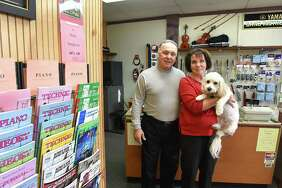 John and Evelyn Butto and their dog Bentley stand in their store Northeast Music which is closing after 39 years on Monday, Nov. 20, 2017 in Latham, N.Y. (Lori Van Buren / Times Union)