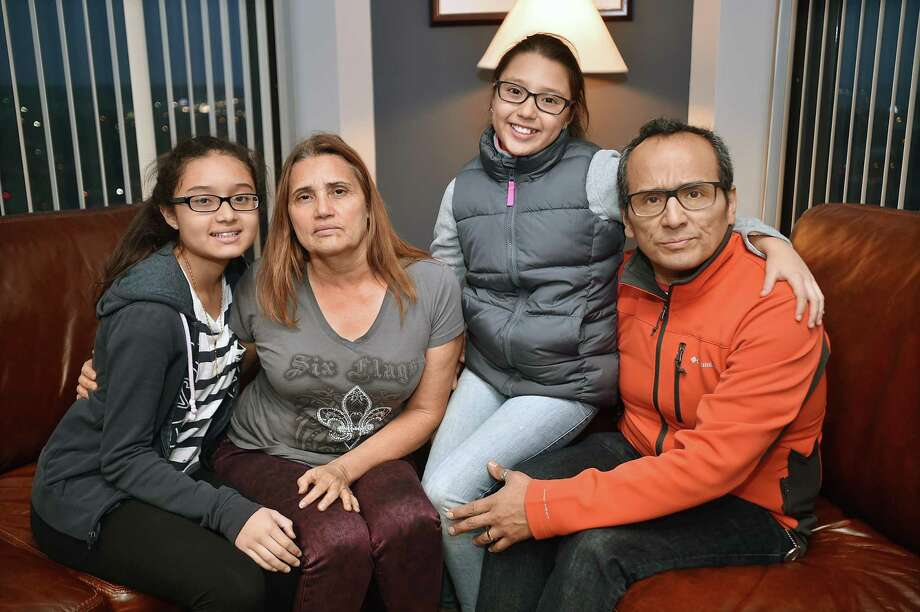 Miriam Martinez, 53, a Stamford mother facing deportation to Guatemala, sits with her husband Raphael Benavides, 46, and their daughters Brianna Benavides, 12, at left, and her 10-year-old sister Allison Benavides, at the New Haven office of their attorney, Glenn Formica. Photo: Catherine Avalone / Hearst Connecticut Media / New Haven Register