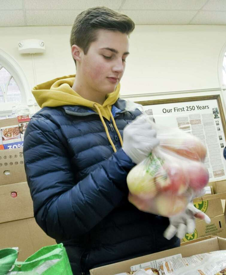Ben Holloway, a student at Wooster School in Danbury, fills bags with apples for Thanksgiving Food Distribution at the Daily Bread Food Pantry in Danbury. Monday, Nov. 20, 2017 Photo: Scott Mullin / For Hearst Connecticut Media / The News-Times Freelance