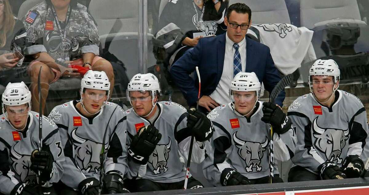 San Antonio Rampage head coach Eric Veilleux (rear) and players watch first period action against the Ontario Reign from the bench on Oct. 7, 2017 at the AT&T Center.