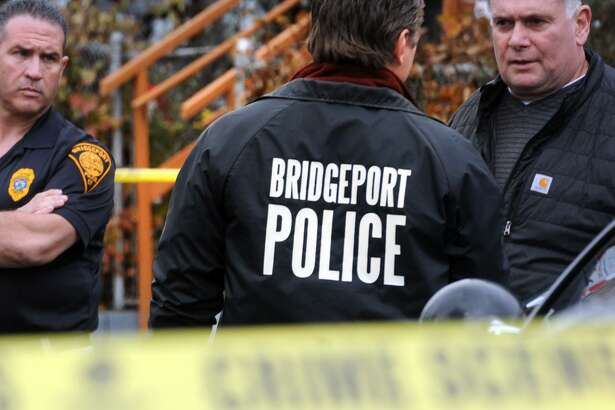 A Bridgeport Police Officer wears a Bridgeport Police jacket a the scene following a shooting incident on Pequonnock Street, in Bridgeport, Conn. Nov. 16, 2017.