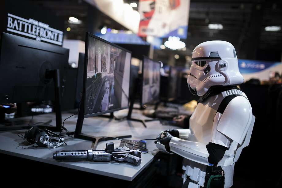 """A fan dressed as a Stormtrooper   plays """"Star Wars: Battlefront II,"""" where players use money to buy """"loot boxes"""" with perks. Photo: Kamil Zihnioglu, Associated Press"""