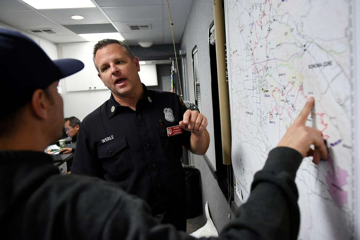 Tim Werle, right, a fire captain with the Los Angeles Fire Department and a lead with CalFire Team 1, talks with supervisor Rene Gonzalez as they work at updating fire map data in the Geographic Information Systems truck at the CalFire camp and operations center at the Sonoma County Fairgrounds in Santa Rosa, Calif, on Thursday October 12, 2017.